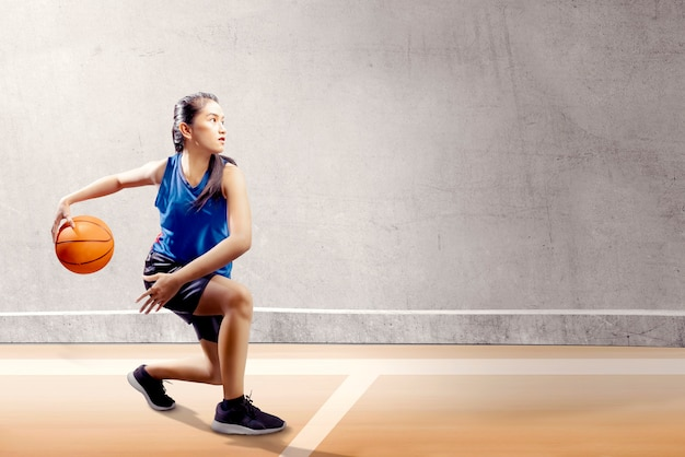 Attractive asian girl in blue sport uniform on basketball pivot moves on the basketball court Premium Photo