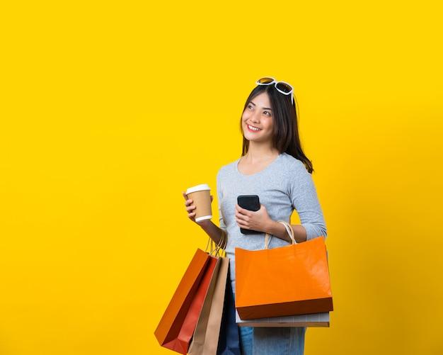 孤立した黄色の壁にショッピングcolofulバッグ、携帯電話、紙のコーヒーカップを運ぶ魅力的なアジアの笑顔の若い女性 Premium写真