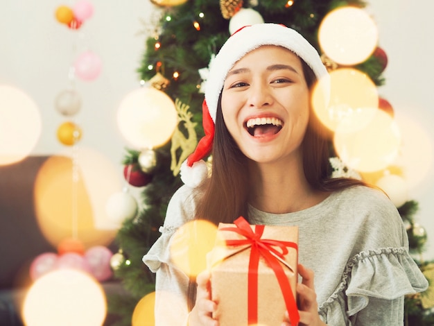 Attractive asian woman holding gift box in hands. Premium Photo