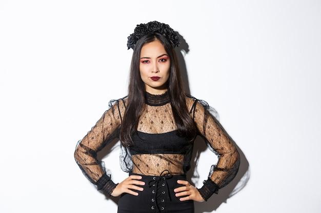 がっかりして懐疑的に見えるハロウィーンの衣装を着た魅力的なアジアの女性。傲慢に見える黒いレースのドレスと花輪の女性、魔女の衣装でトリックオアトリート、白い背景に立っています。 無料写真