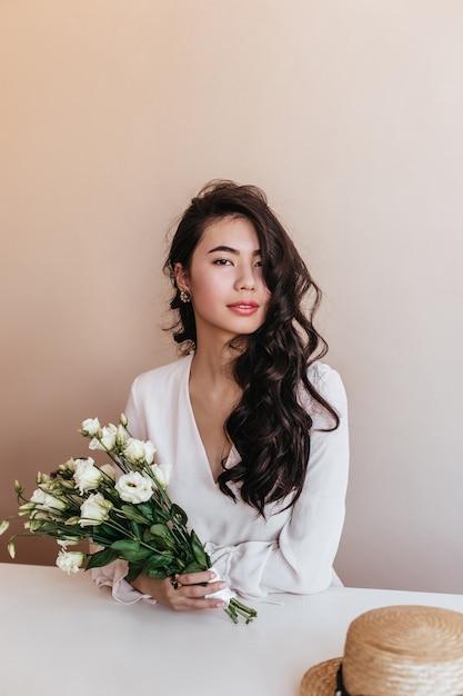 カメラを見ている花を持つ魅力的なアジアの女性。トルコギキョウの花束を保持している長い髪の巻き毛の中国人女性。 無料写真