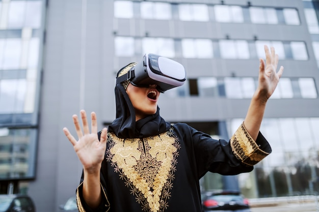 Attractive astonished young muslim woman in traditional wear standing in front of corporate building and using vr goggles. Premium Photo