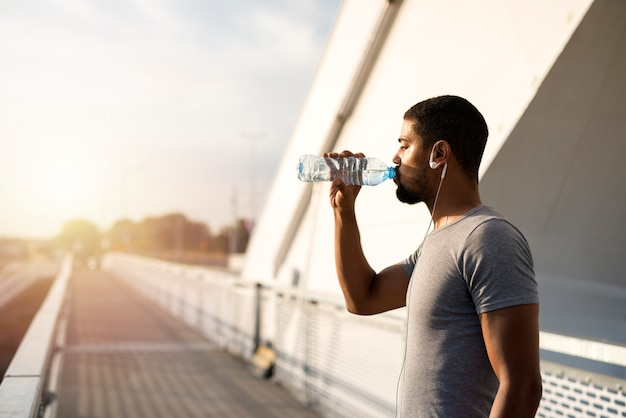 Attractive athlete holding bottle of water and drinking before training Free Photo