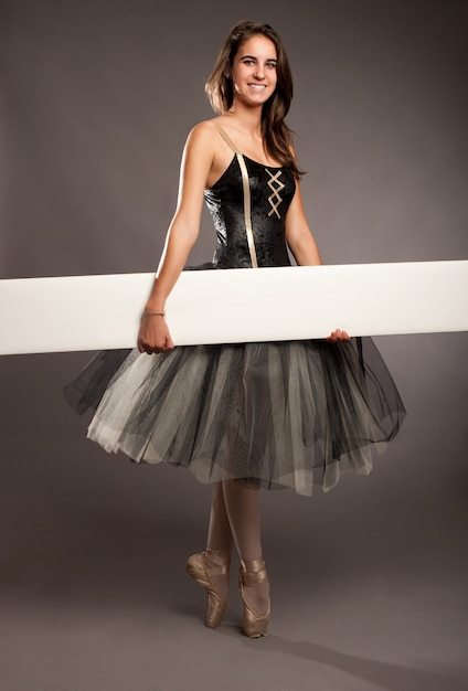 Attractive ballerina on tiptoe holding a white banner Premium Photo