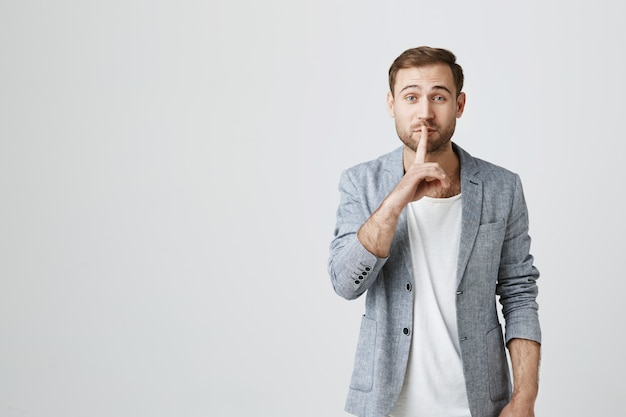 Attractive bearded guy asking keep quiet, hush Free Photo