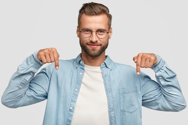 Привлекательный бородатый парень позирует у белой стены Бесплатные Фотографии