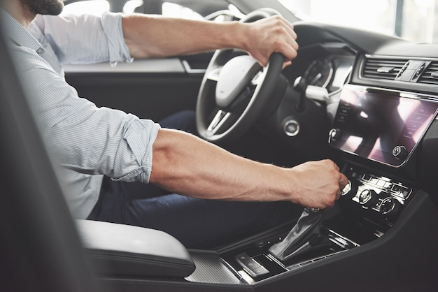 Attractive bearded happy man in good car. Free Photo
