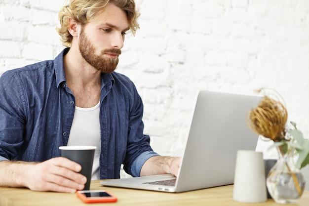 魅力的なひげを生やした男性起業家がモダンなカフェで昼食時に一般的なラップトップコンピューターで作業しながらお茶やコーヒーを飲みます。遠くの仕事にノートブックpcを使用して深刻な若いフリーランスの労働者 無料写真