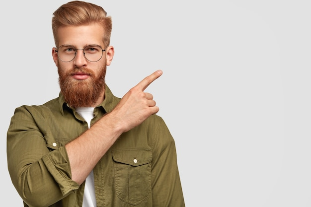Attractive bearded male with thick ginger beard and hair, appealing look, points at upper right corner Free Photo