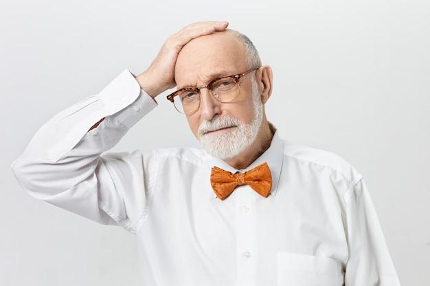 Привлекательный бородатый пенсионер в белой рубашке и оранжевом галстуке-бабочке, держащий руку на своей лысине, ему грустно, потому что он слишком быстро состарился. возраст, пенсия и концепция зрелости Бесплатные Фотографии