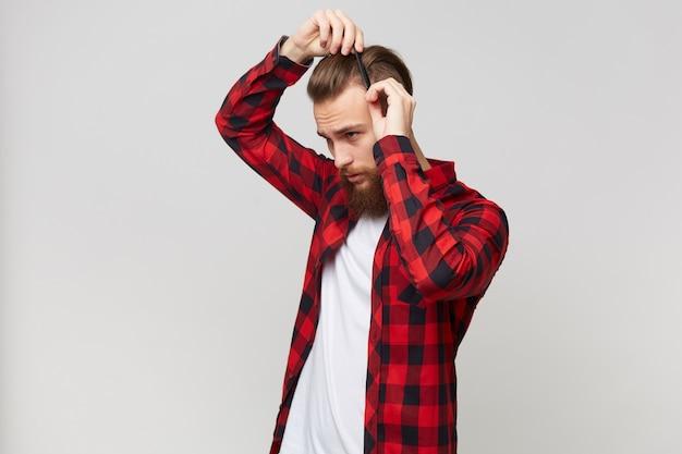 Привлекательный бородатый молодой человек в рубашке, стоящий в профиль, делает современную прическу, ухаживая за волосами с помощью гребня, изолированного на белом фоне Бесплатные Фотографии