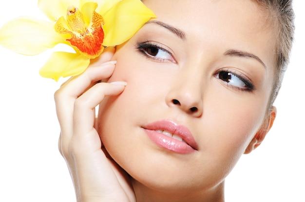 白で隔離の耳から花と魅力的な美しさアジアの女性の顔 無料写真