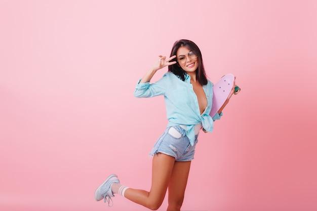 カジュアルな夏の装いで踊る魅力的な黒髪の女性モデル。片足でポーズをとって笑っているスポーティな靴で洗練されたヒスパニック系の女の子。 無料写真