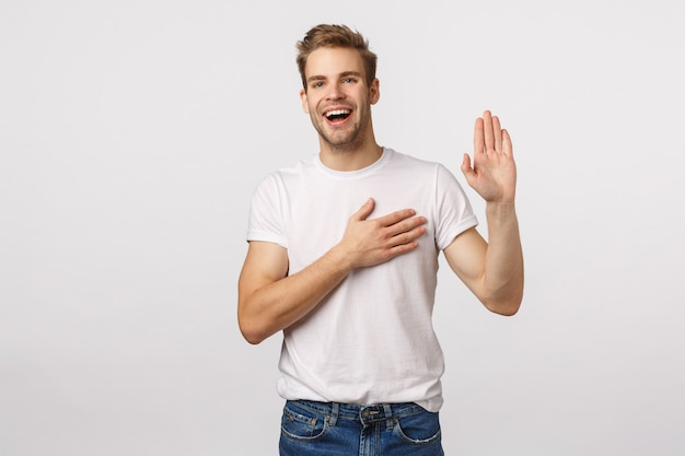 Attractive blond bearded man in white t-shirt raises one hand and holds another on heart Premium Photo