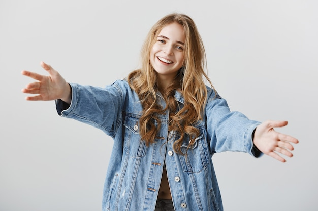 Attractive blond girl smiling happy and spread hands sideways for hug, embracing or taking something Free Photo