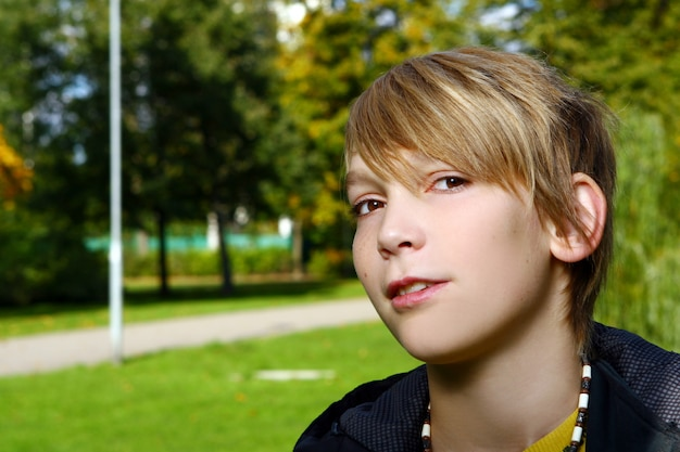Attractive blonde boy posing in park Free Photo