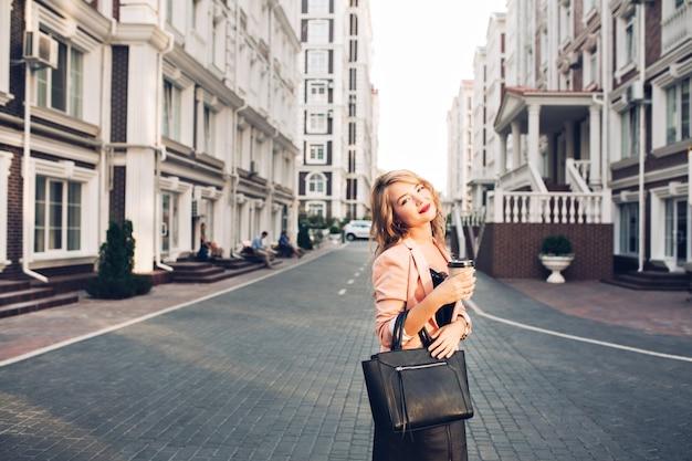 通りにコーラルジャケットのコーヒーカップと歩いてほのかの唇と魅力的なブロンドの女の子。彼女は黒いバッグを着ています 無料写真