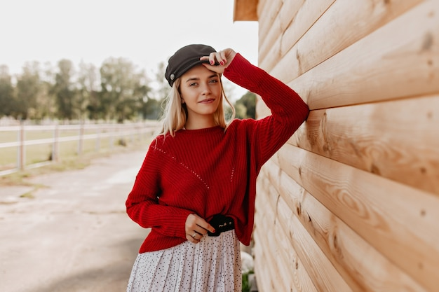 Attractive blonde with natural makeup looking with tenderness . young woman in red pullover and stylish hat posing near the wooden house. Free Photo