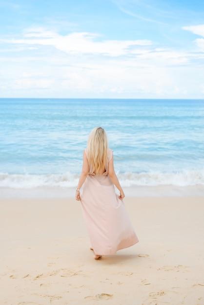 Привлекательная блондинка молодая женщина стоит на белом песке Premium Фотографии