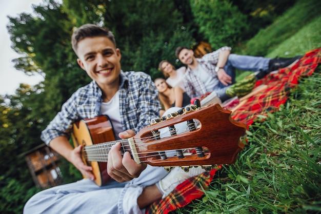 Симпатичный мальчик сидит в траве и играет на гитаре, он на пикнике с тремя друзьями. Premium Фотографии