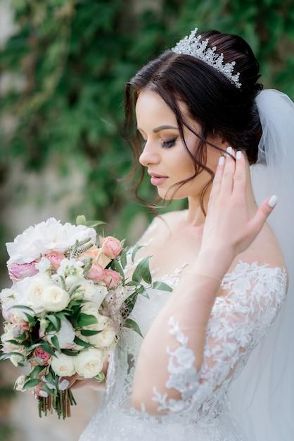 Привлекательная невеста в короне с красивым свадебным букетом из белых эустом и розовых роз Бесплатные Фотографии
