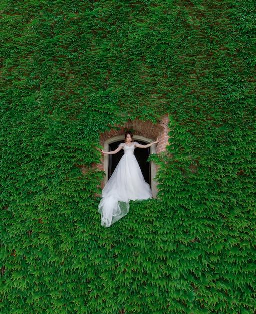 緑の葉で覆われた壁に作られた穴に魅力的な花嫁が立っています。 無料写真