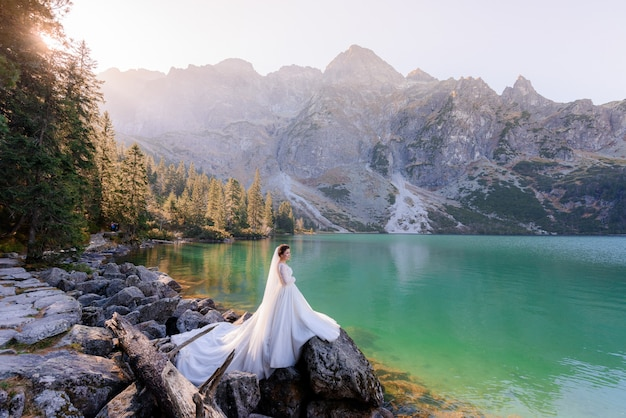 Attractive bride is standing near highland lake with picturesque view of autumn mountains Free Photo