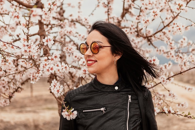 Attractive brunette girl near a almond tree with many flowers Premium Photo