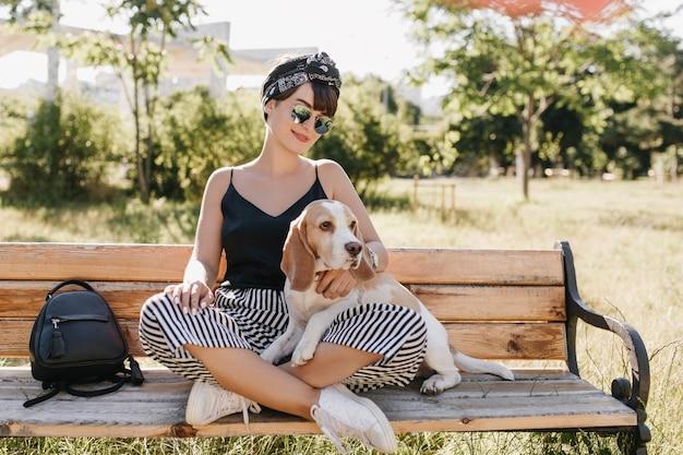 足を組んでビーグル犬をなでて座っている縞模様のズボンの魅力的なブルネットの女性。晴れた日に革のバッグの近くに子犬と一緒にベンチで休んでいるスタイリッシュな笑顔の女の子 無料写真