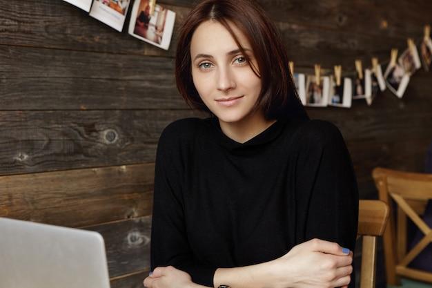 Attraente ragazza studentessa bruna che indossa un elegante abito nero tenendo le braccia conserte mentre era seduto davanti al computer portatile, lavorando sul progetto di diploma online, usando la connessione wi-fi gratuita durante la pausa caffè Foto Gratuite
