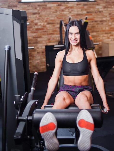 체육관에서 운동 기계에서 다리 확장 운동을하는 운동복에 매력적인 갈색 머리 여자 프리미엄 사진