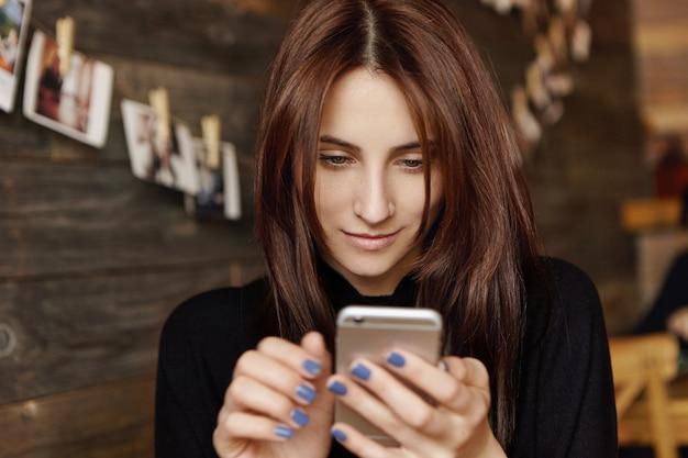 Текстовое сообщение привлекательной женщины брюнет печатая на родовом smartphone пока ждущ друга, сидя на кафе. милые европейские девушки смотрят фотографии в социальных сетях Бесплатные Фотографии