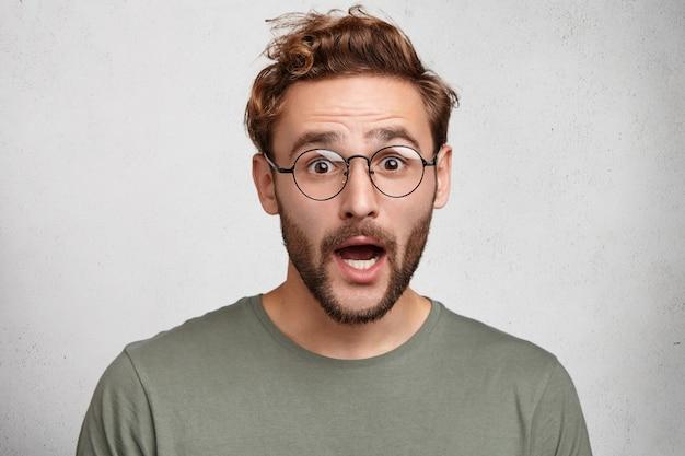 カジュアルなtシャツを着た魅力的なバグの目をしたヒップスターの男または賢い学生、衝撃の悲鳴、 無料写真