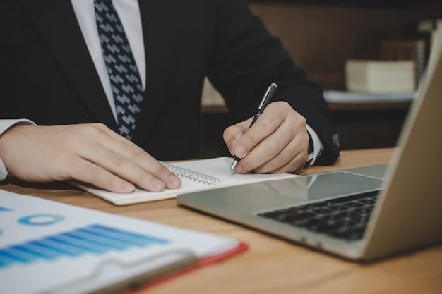 Привлекательный бизнесмен в черном костюме работая и писать на отчете о документе на столе в офисе комнаты встречи дома, инвестициях, контракте, цифровом он-лайн маркетинге и концепции финансового дела Premium Фотографии