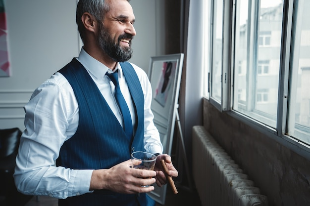 Attractive business man with a cigar and a glass of whiskey. Premium Photo