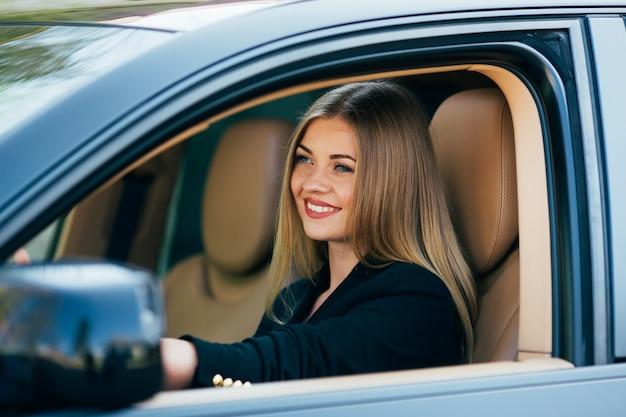 彼女の車を笑顔で運転しているサングラスを持つ魅力的なビジネス女性。 無料写真