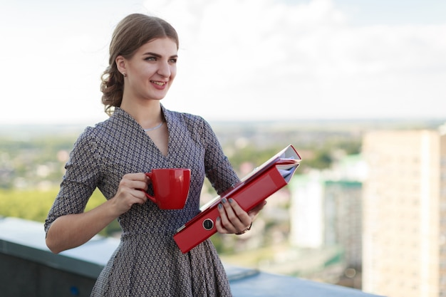 Attractive businesslady in patterned dress stand on the roof and hold paper folder and red cup Premium Photo