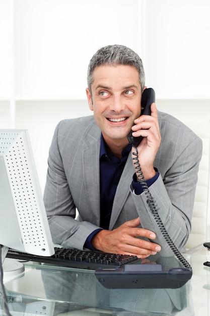 Attractive businessman on phone at his desk  Premium Photo