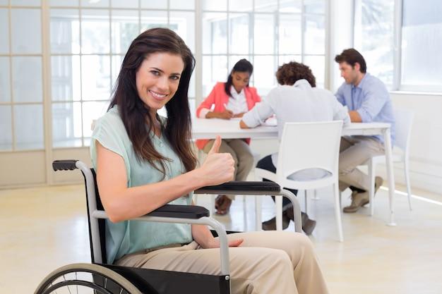 車椅子の魅力的な実業家はカメラに親指を与える Premium写真