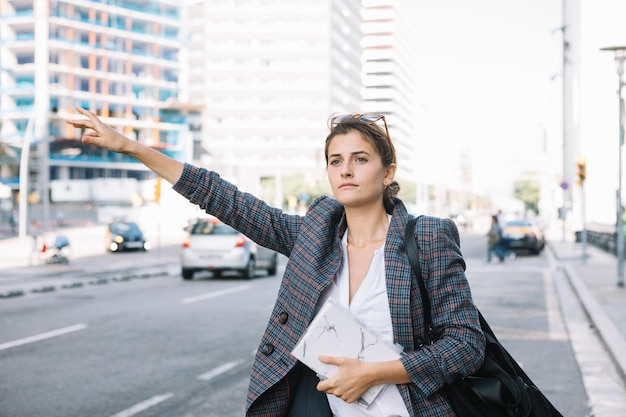 Attractive businesswoman raising her hand to call cab on city road Free Photo