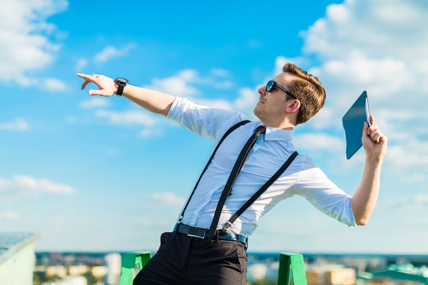Attractive busunessman in white shirt, tie, braces and sunglasses throw tablet from roof Premium Photo
