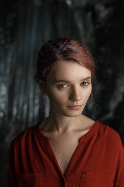 Attractive caucasian girl in red shirt with deep neckline and open clavicles standing against blurred fabric background Premium Photo