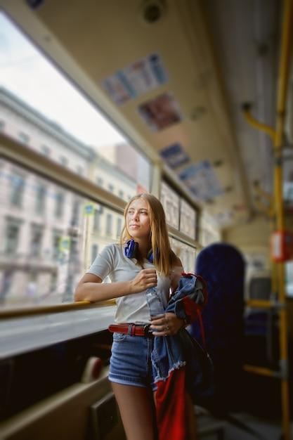 긴 금발 머리와 헤드폰을 가진 약 25 세의 매력적인 백인 잠겨있는 여성이 대중 교통에 서 있습니다. 프리미엄 사진