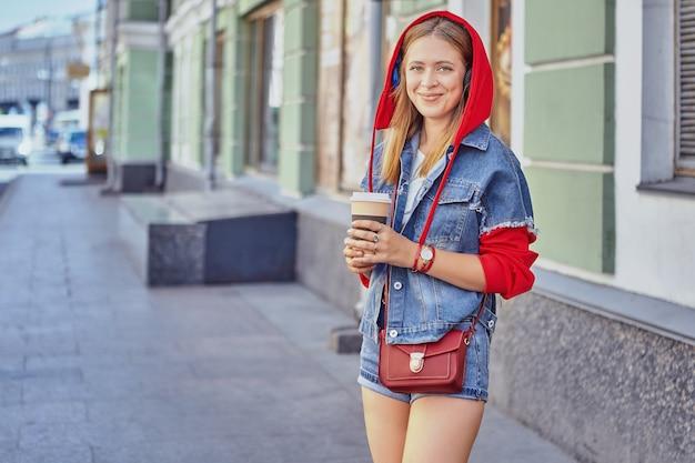 매력적인 백인 젊은 명랑 한 여자 약 25 세 빨간 까마귀와 긴 금발 머리를 가진 종이 컵에서 커피를 마시고있다. 프리미엄 사진