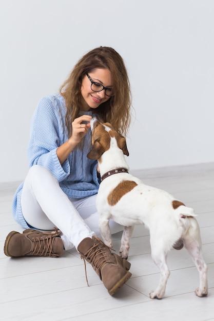 彼女のお気に入りのペットと遊ぶ青いセーターの魅力的な陽気な女性 Premium写真