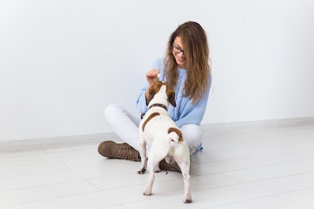 彼女のペットと遊ぶ青いセーターの魅力的な陽気な女性 Premium写真