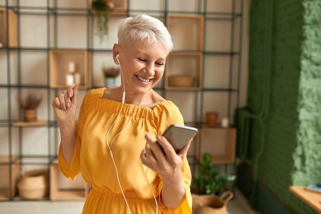 携帯電話を使用して、イヤホンで音楽を聴いて、踊って、幸せな楽しい表情を持っている黄色のドレスを着た魅力的な陽気な女性年金受給者 無料写真