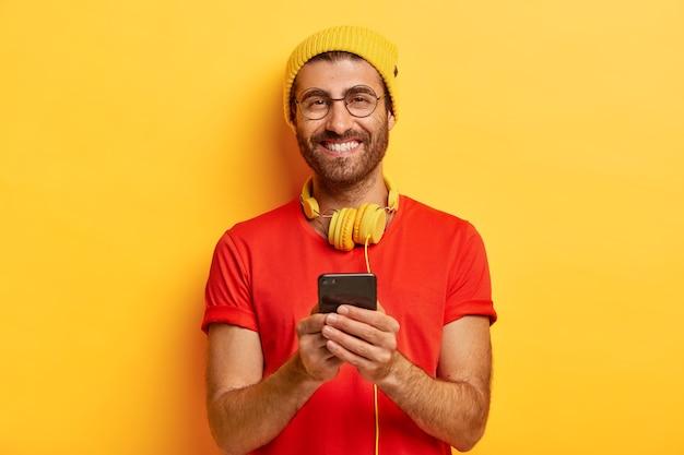 剛毛の魅力的な陽気な男、明るい帽子と赤いtシャツを着ています 無料写真