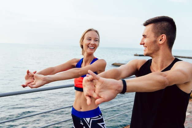 Attractive cheerful young couple doing stretching exercises for arms while working out Free Photo