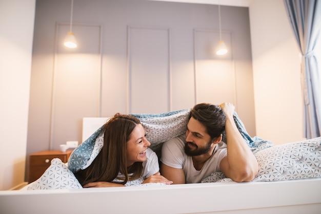 お互いに笑みを浮かべて毛布の下に横たわっている魅力的なカップル。 Premium写真
